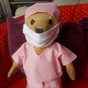 Teddy bear wearing hospital scrubs and mask