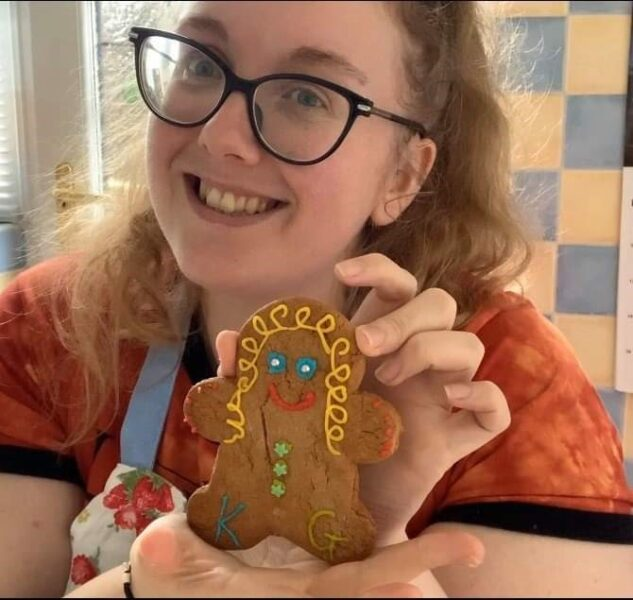 Practitoner Kirsty holding a home made gingerbread cookie decorated with icing inspired by The Gingerbread Man story.