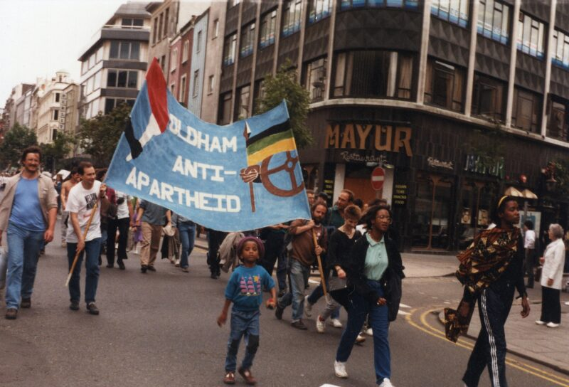 This photograph shows the banner in use on a march in Manchester.