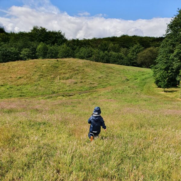 Toddler running through long grass at Tandle Hill