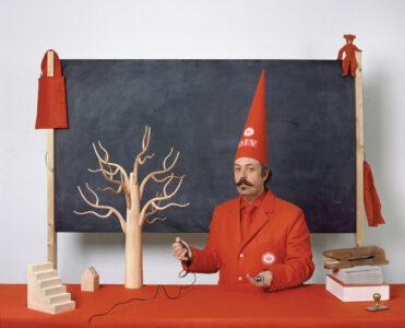 Benedict Philips in Red Hat in front of blackboard