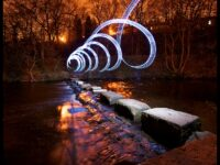 Light Photo showing a lit up spiral on stepping stones across a river