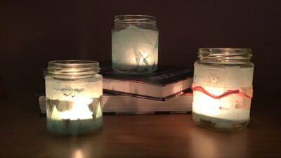 Completed Jam Jar tea-lights lit up on table with books.