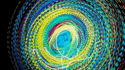 Circular spiral of multi-coloured lights produced by light painting.