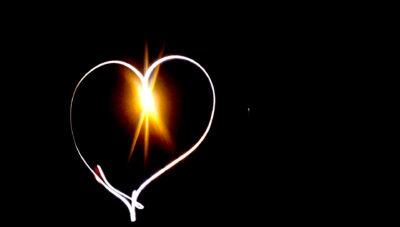Heart shape in light against black background.