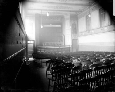Black and white photo of Old lecture theatre with chairs and stage.