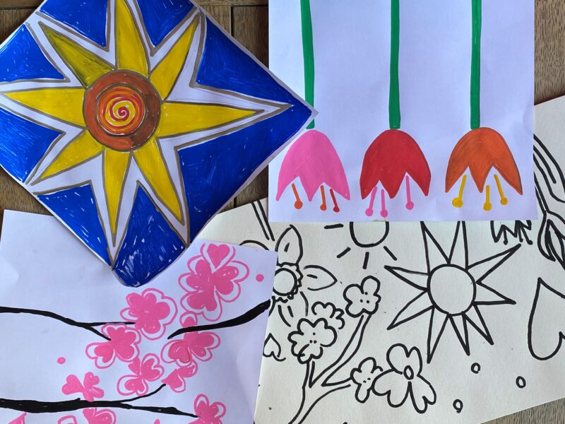 Example of designs on paper including tulips, a sun on blue background