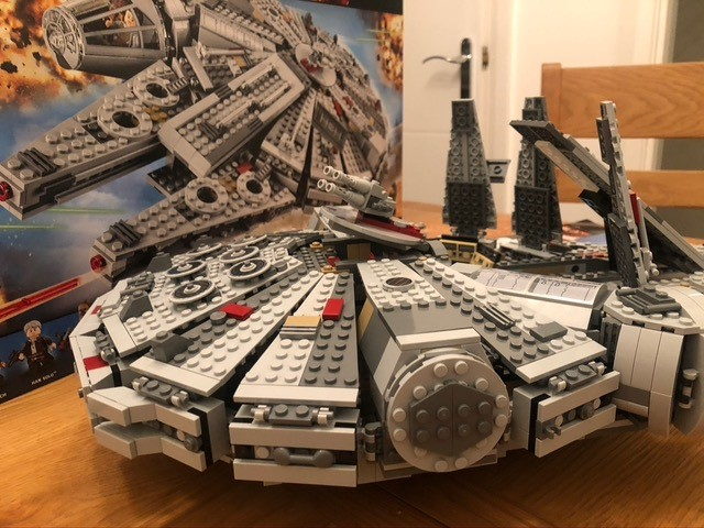 Lego Star Wars Millennium Falcon with box on table.