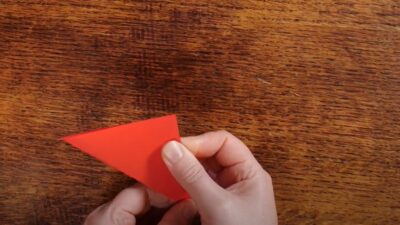 Artist folding a square of red paper into a triangle.