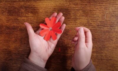 Red paper flower opened and displayed in artists hand.