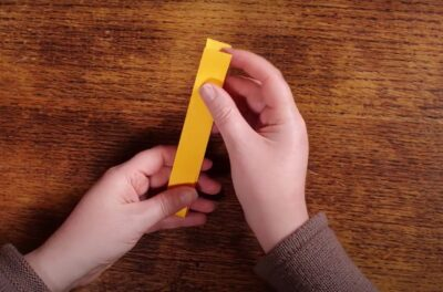 Artist is folding the yellow strip of paper in half.