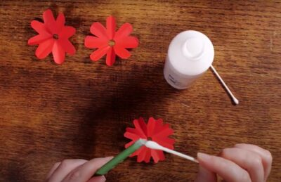 Artist is gluing the top of the stem and the red petals with a cotton bud and PVA glue.