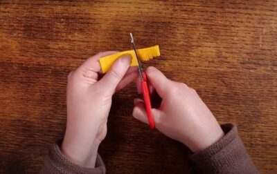 Artist is cutting tassles into the folded yellow stip of paper using scissors. Cuts are made halfway up the paper.