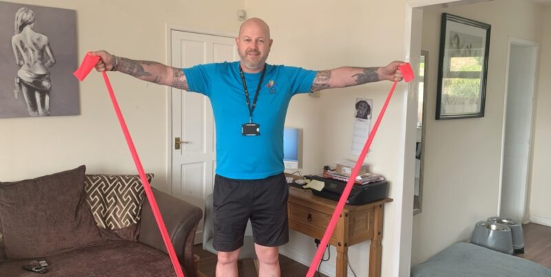 Jason in his lounge using stretching elastics to exercise.