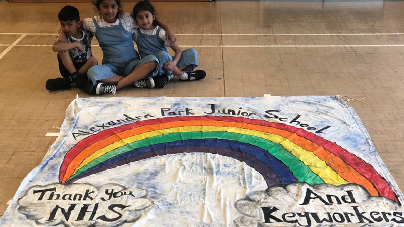 Three children sat on the ground of an assembly hall with a rainbow banner with words Alexandra Park Junior School, Thankyou NHS and Keyworkers.