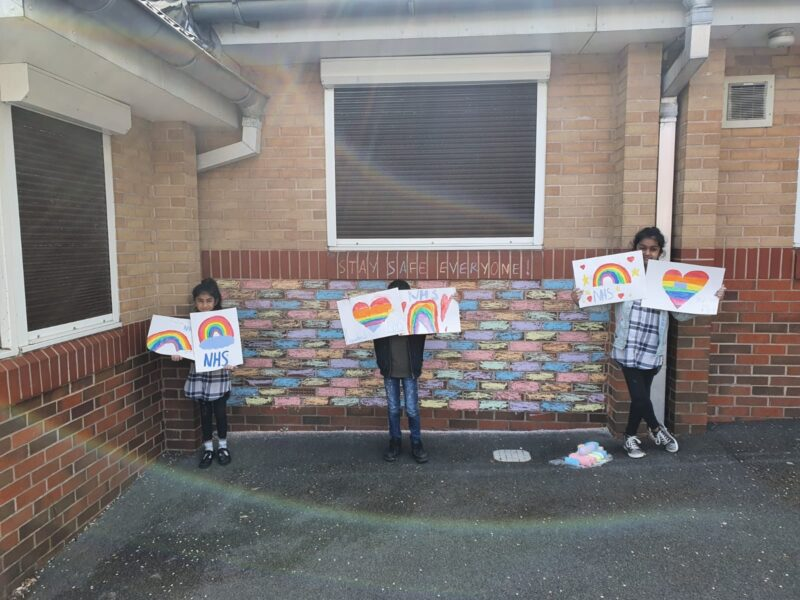 Three children standing outside the school holding paintings and drawings of hearts and rainbows for the NHS.