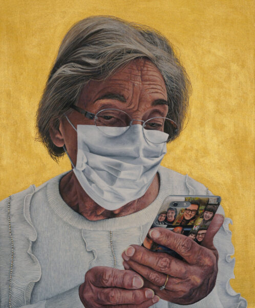 Older women wearing facemask, looking down at her smartphone.