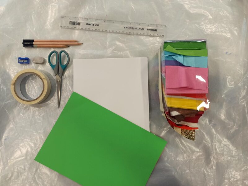 Collection of arts materials including paper, ruler, pencils scissors, masking tape and rubbers