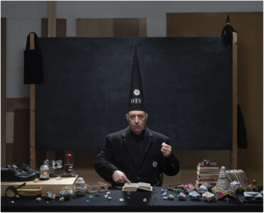 Benedict Phillips dressed in black with Black DIV hat in front of blackboard