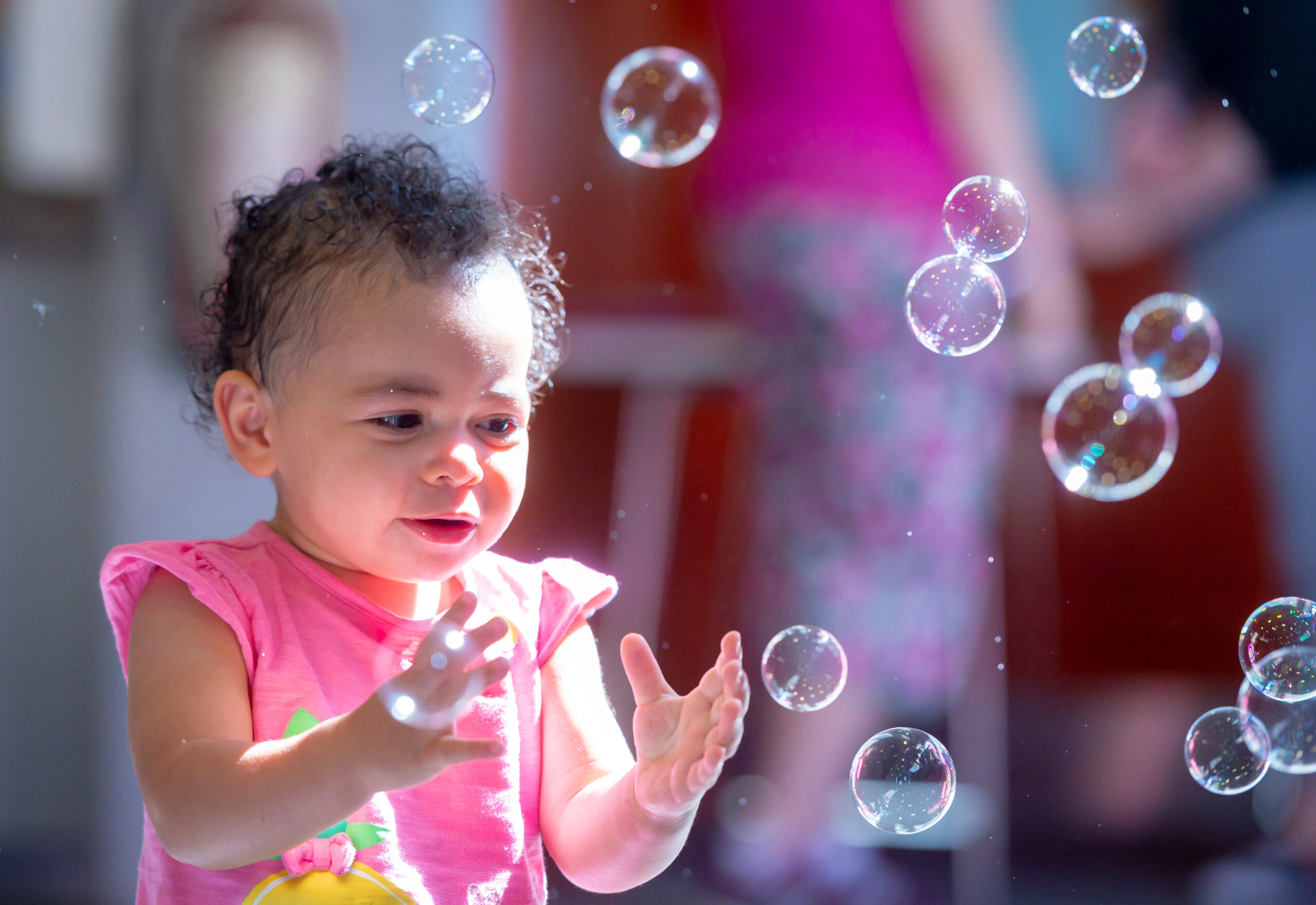 Image of a toddler playing with bubbles