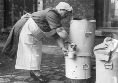 Black and white photo of a women with apron and headscarf getting water from a tea urn.