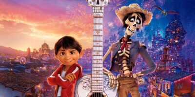 Colourful animated film poster showing a young boy a guitar and a skeleton.